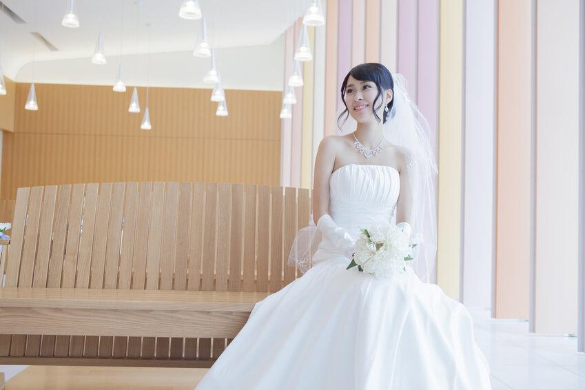 教会で座るブーケを持ったウエディングドレス姿の女性